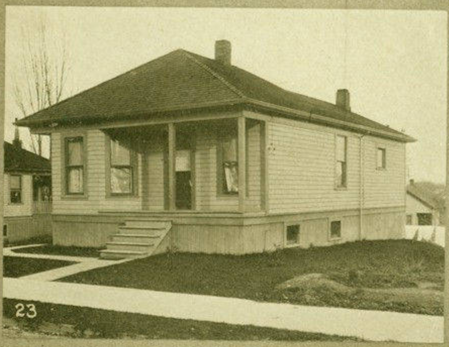 Black and white photograph of a small but somewhat deep single-story house, with a porch covering two-thirds of the front. It is connected to bright white sidewalk by a simple, wide set of five stairs. Home of Frank Smith and Sadie Tipps