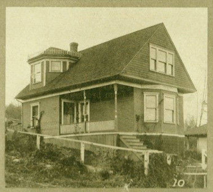 A house with turreted back dormer is up a flight of stairs from the street. The stairs lead up next to a bay window on front of the house to a long porch. Fence posts are in with a railing, but no slats have been added yet. Next door is a dirt lot.