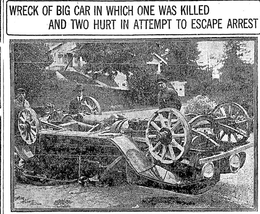 """Newspaper clipping with photo of 1910s automobile lying upside down. Police officers and a detective stand behind it. Above it is a headline """"Wreck of big car in which one was killed and two hurt in attempt to escape arrest""""."""