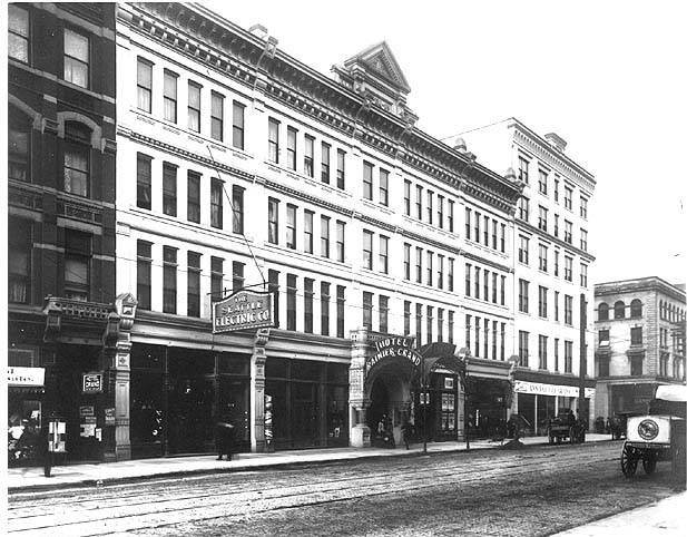 View of three story hotel with Hotel Rainier Grand over entrance, 22 windows wide on main building with 5 story addition on right corner that is 9 windows wide.